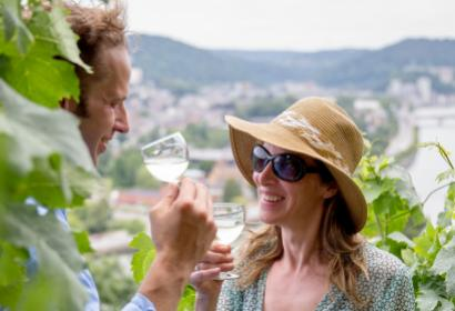 Couple, in the Le Clos des Prébendiers vineyard in Huy, raising a toast